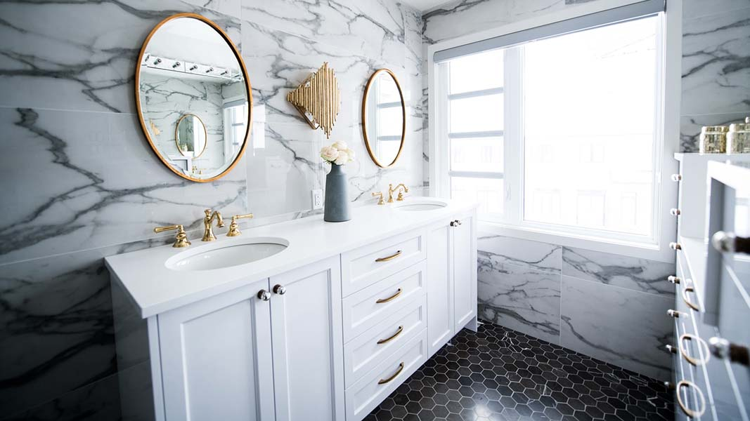 grey and white marble tiled luxury bathroom with gold round mirrors and white vanity